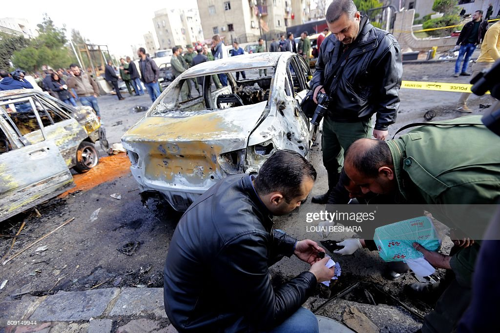 Syrian security forces and policemen inspect the site of a suicide attack at a police officer's club in the Masaken Barzeh district of the capital Damascus on February 9, 2016. The Syrian Observatory for Human Rights said about 20 people had also been wounded, adding that policemen were among the dead and injured. BESHARA
