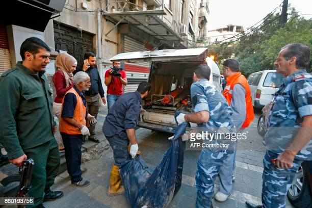 Syrian security forces carry the remains of a reported suicide bomber following an attack near the main police headquarters in Syria's capital...