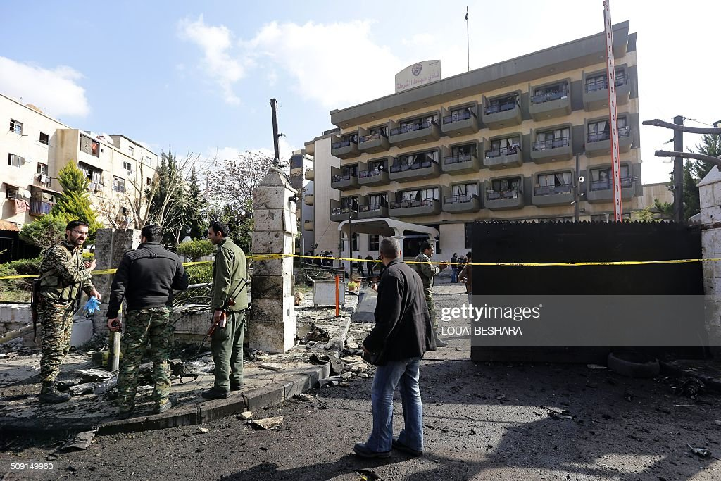 Syrian security forces gather at the site of a suicide attack at a police officer's club in the Masaken Barzeh district of the capital Damascus on February 9, 2016. The Syrian Observatory for Human Rights said about 20 people had also been wounded, adding that policemen were among the dead and injured. BESHARA