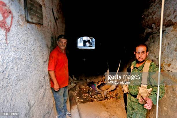 Syrian security forces gather near the site of an attack near the main police headquarters in Syria's capital Damascus on October 11 2017 Three...