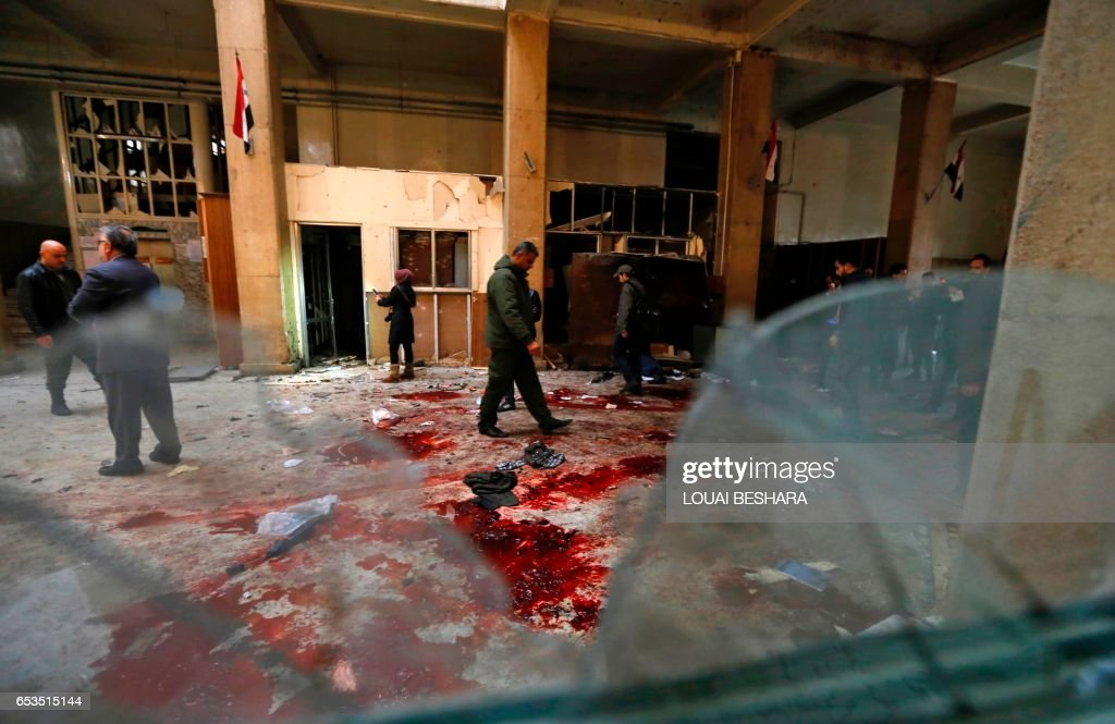 TOPSHOT - Syrian security forces inspect the scene of a reported suicide bombing at the old palace of justice building in Damascus on March 15, 2017. Two suicide bombings hit Damascus including the attack at the central courthouse that left at least 32 dead, as Syria's war entered its seventh year with the regime now claiming the upper hand. / AFP PHOTO / Louai Beshara