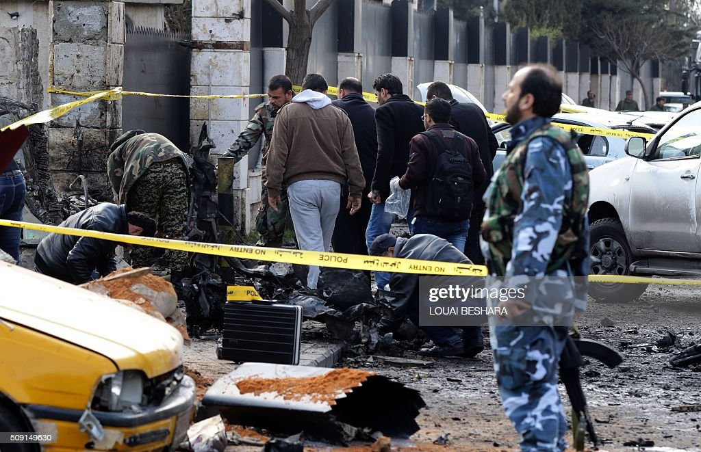 Syrian security forces inspect the site of a suicide attack at a police officer's club in the Masaken Barzeh district of the capital Damascus on February 9, 2016. The Syrian Observatory for Human Rights said about 20 people had also been wounded, adding that policemen were among the dead and injured. BESHARA