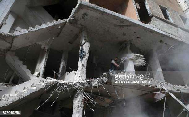 Syrian shovels away debris from the higher floor of a building that was reportedly shelled by regime forces in the rebelheld Eastern Ghouta town of...