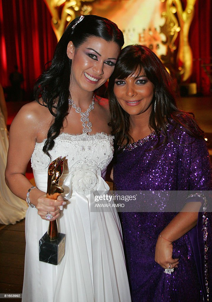 Syrian singer Asala (R) poses with Nadine al-Rassi as she holds her Murex d'Or award for best Lebanese actress in a leading role in 'Ebni' (My Son) at the Casino du Liban in Jounieh, north of Beirut, late June 20, 2008. The annual Murex d'Or awards Lebanon's and the Middle East's equivalent to the Oscars in importance, but honour the best in film, television and music.