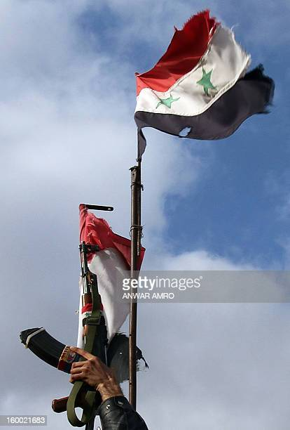 Syrian soldier lifts up his machine gun next to the Syrian flag in the southern city of Sweida on January 23 2013 The two provinces are diametrically...
