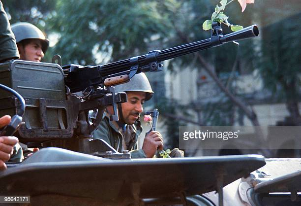 A Syrian soldier member of the joint Arab peacekeeping force to Lebanon smells a rose atop an armoured personnel vehicle in November 1976 in Beirut...