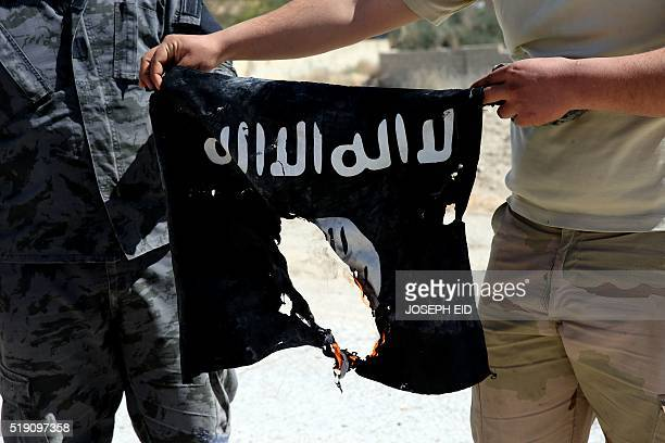 Syrian soldier sets fire on April 4 2016 to an Islamic State group flag after Syrian troops regained control the previous day of alQaryatain a town...