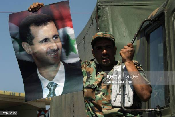 Syrian soldier waves a picture of the Syrian president Bashar Assad as he crosses the LebaneseSyrian border April 26 2005 in Jdaidet Yabous Syria...