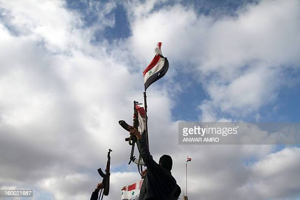 Syrian soldiers lift up their machine gun next to the Syrian flag in the southern city of Sweida on January 23 2013 The two provinces are...