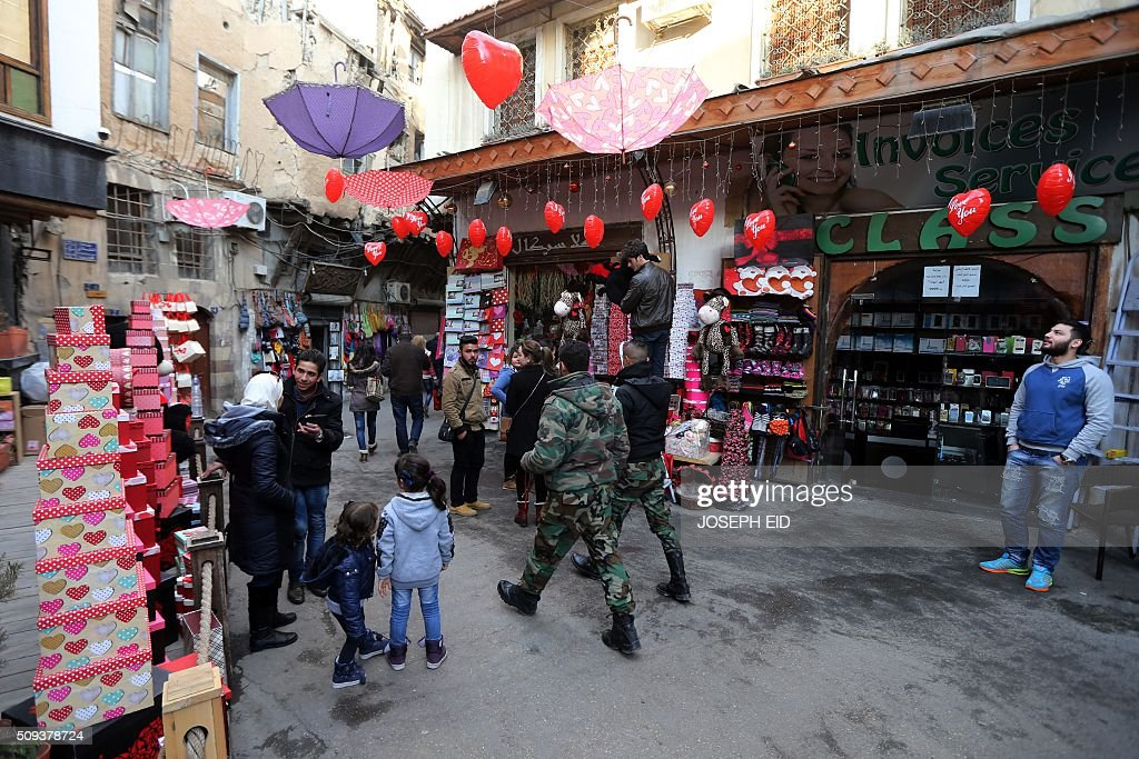 Syrian soldiers walk past shops displaying gifts for Valentine's day in Damascus on February 10, 2016. / AFP / JOSEPH EID