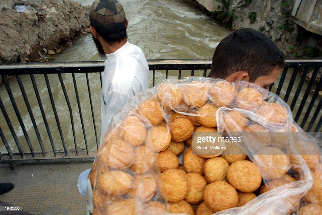 Syrian street vendor passes the Barada River with sweets April 19 2003 in Damascus Syria Foreign ministers of countries bordering Iraq including...