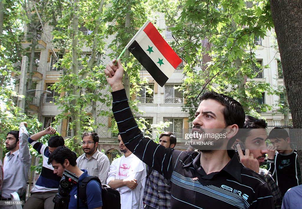 A Syrian student, waving the Syrian flag, as he and Iranian colleagues attend an anti-Israeli demonstration in front of the United Nations offices in Tehran, on May 6,2013, to condemn Israeli air strikes on targets near the Syrian capital Damascus. Israeli raids on Syrian targets at the weekend killed at least 15 soldiers, a watchdog said, as UN chief Ban Ki-moon led calls for restraint to prevent the war spilling over borders.