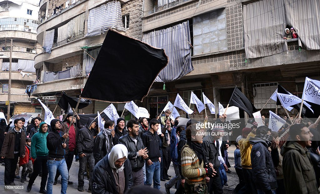 Syrian supporters of the Al-Nusra group wave flags as they march during an anti-regime demonstration after the weekly Friday prayers in the Bustan al-Qasr district of the northern city of Aleppo on February 8, 2013. Syrian forces shelled rebel belts, the Syrian Observatory for Human Rights said, as an army offensive raged into a third straight day.