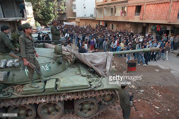 Syrian tankists standing a top a Russianmade tank oversee 12 January 1990 march through southern Beirut suburb by proIranian Hezbollah fighters...