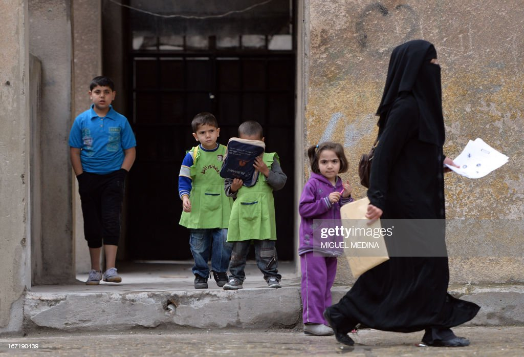 A Syrian teacher walks past children at the Nur al-Haq school in the northern city of Aleppo on April 22, 2013. The European Union offered fresh aid to Syria's opposition, easing an EU oil embargo in favour of the rebels fighting President Bashar al-Assad, but stopping short of supplying offensive weapons.