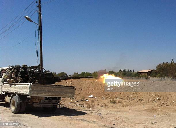 Syrian troops fire a heavy machine gun mounted on a pickup truck in the Eastern Ghouta area on the northeastern outskirts of Damascus on August 30...