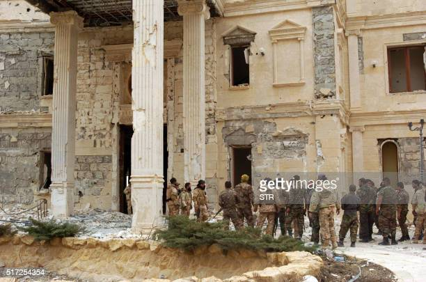 Syrian troops stand next to a mansion belonging to the Qatari royal family on the outskirts of the ancient city of Palmyra on March 24 2016 Backed by...