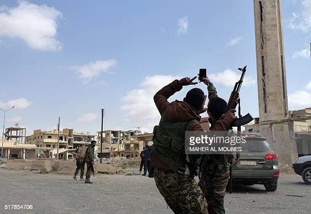Syrian troops take a selfie as they walk in the damaged streets of the residential neighbourhoods in the modern town adjacent to the ancient Syrian...