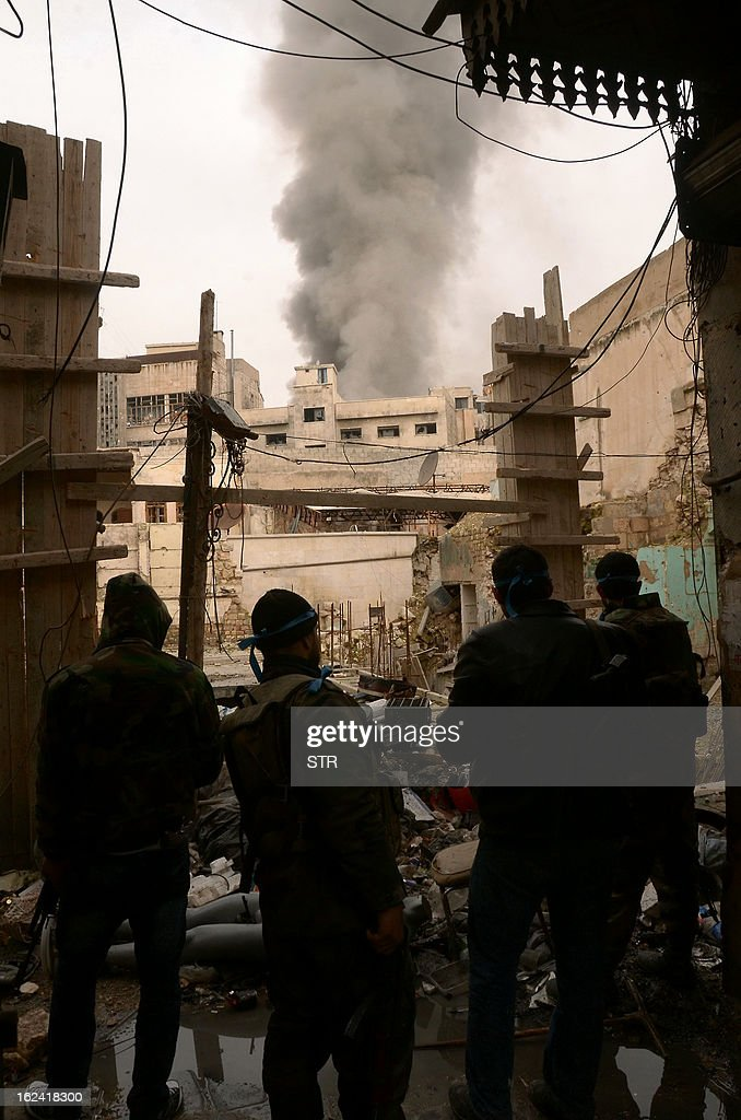 Syrian troops take position in the heavily damaged Zahrawi souq during a patrol in the old city of Aleppo as smoke billows in the background on February 23, 2013. The umbrella opposition National Coalition condemned world powers for failing to act to stop the slaughter in Syria, as missiles killed at least 29 in second city Aleppo.