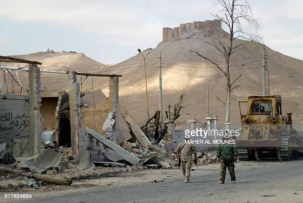 Syrian troops walk in the destroyed streets of the residential neighbourhoods backdropped by the citadel in the modern town adjacent to the ancient...