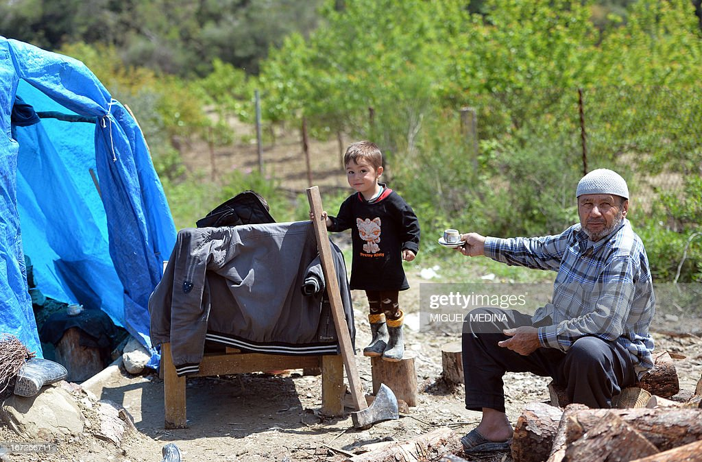 A Syrian Turkman offers tea to his grandson next to his tent at a make-shift refugee camp some kilometers away from the Syria-Turkey border on April 23, 2013. There are an estimated four million people displaced inside Syria and the 1.2 million refugees in neighbouring countries.