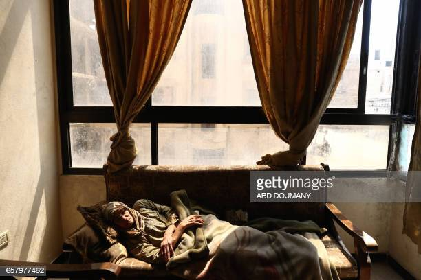 TOPSHOT Syrian Umm Ahmad a seventythreeyear old widow who was displaced from the alMaliha area due to the ongoing fighting is seen inside her home in...