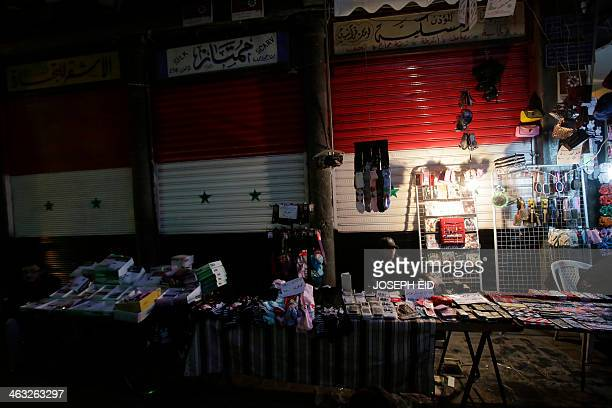 A Syrian vendor displays items for sale in front of shutters painted with the Syrian national flag's colours at alHamidiyah market in old Damascus on...