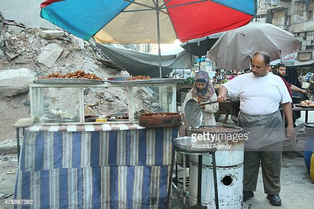 Syrian vendors prepare Ramadan desserts on stands during the holy month of Ramadan in a historical bazaar which is heavily damaged by Asad regime...