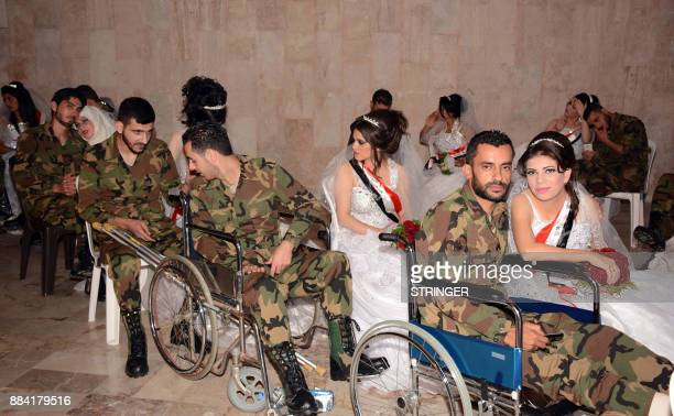 Syrian veterans dressed in army fatigues sit with their brides who are wearing sashes bearing the colours of the Syrian flag during a mass wedding in...