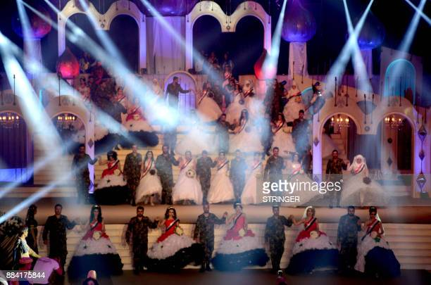 Syrian veterans dressed in army fatigues stand on the stage with their brides who are wearing sashes bearing the colours of the Syrian flag during a...