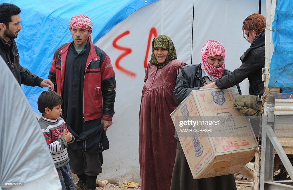 A Syrian volunteer distributes heaters to displaced Syrian families at the refugee camp of Qah along the Turkish border in the village of Atme in the northwestern province of Idlib, on February 7, 2013. More than half of the estimated 300,000 Syrian refugees who have fled to Lebanon are not receiving the medical treatment they need because of high costs, Doctors Without Borders (MSF) said.