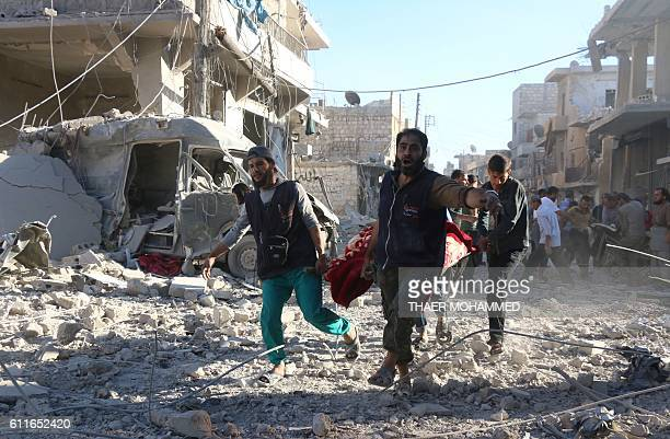 TOPSHOT Syrian volunteers carry an injured person on a stretcher following Syrian government forces airstrikes on the rebel held neighbourhood of...