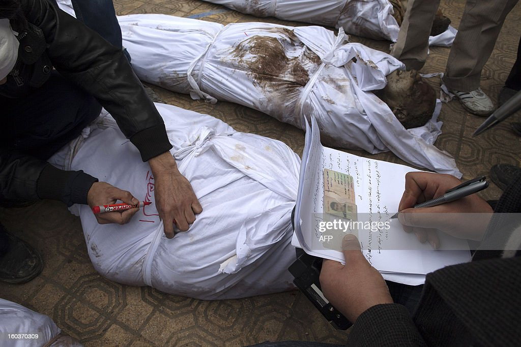 Syrian volunteers write the name of a dead man on a shroud after he was recognised by his relatives in the grounds of the courtyard of the Yarmouk School, in the Bustan al-Qasr district of Aleppo on January 30, 2013. Syria's opposition charged that 'global inaction' was giving Bashar al-Assad's regime a license to kill, a day after dozens of young men were found shot execution-style in the city of Aleppo. AFP PHOTO/JM LOPEZ