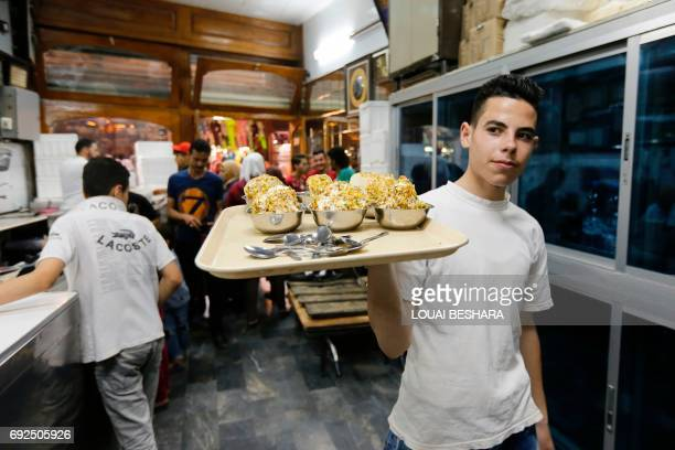 A Syrian waiter serves traditional icecream at the famous 'Bagdash' sweet shop in the Hamidiyeh popular market in the old part of the capital...