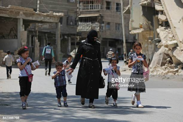 Syrian walk along a destroyed street in the rebelheld town of Douma on the eastern outskirts of Damascus as Muslims celebrate the third day of the...