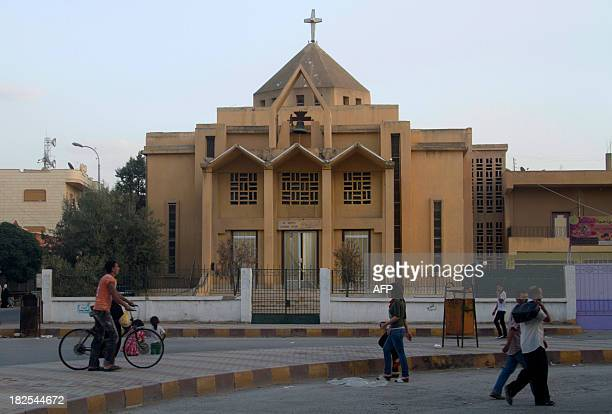 Syrian walk in front of the Armenian Catholic Church of the Martyrs in the northern rebelheld Syrian city of Raqqa on September 16 2013 Islamic State...
