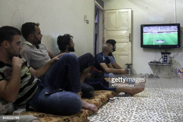 TOPSHOT Syrian watch the FIFA World Cup 2018 qualification football match between Iran and Syria played in Tehran in the rebel held town of Binnish...