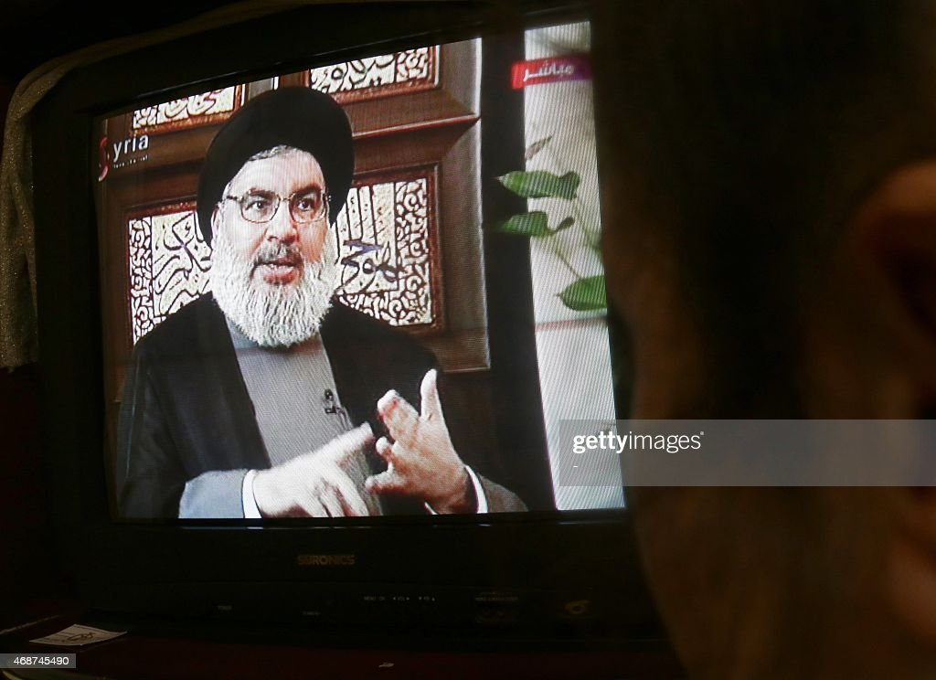 A Syrian watches an interview of Hassan Nasrallah, the head of Lebanon's militant Shiite Muslim movement Hezbollah, screened on Syria's official television channel Al-Ikhbariya on April 6, 2015 in Damascus.