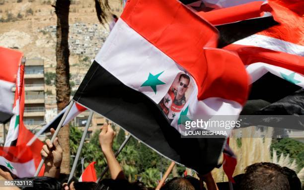 A Syrian waves a Syrian flag bearing a portrait of the Syrian president in Umayyad Square in Damascus as fans gathered to watch a live broadcast of...