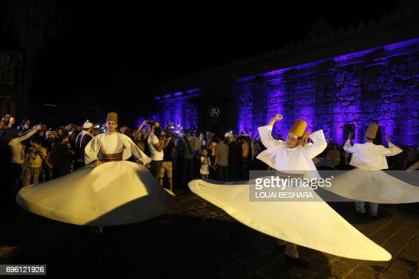Syrian whirling dervishes perform in a celebration during the Muslim holy month of Ramadan outside the Umayyad Mosque in the old city of the capital...