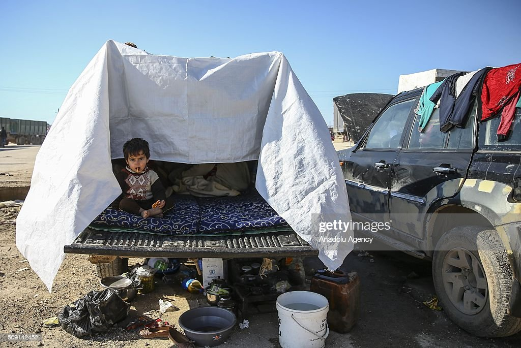 A Syrian, who flee the attacks of Assad Regime and Russian air forces, gestures as he and his family try to live inside their vehicle as they barely covered it with blankets and tarpaulins, at a refugee camp at the Bab al-Salameh border crossing on Turkish-Syrian border near Azaz town of Aleppo, Syria on February 09, 2016.