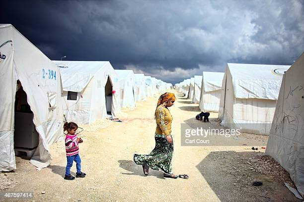 Syrian woman and child walk between tents in Suruc refugee camp on March 25 2015 in Suruc Turkey The camp is the largest of its kind in Turkey with a...