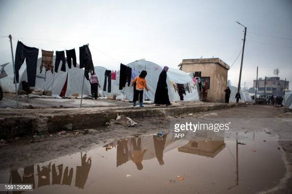 A Syrian woman and child walk next a washing line at a refugee camp near the northern city of Azaz on the SyriaTurkey border home to more than 7000...