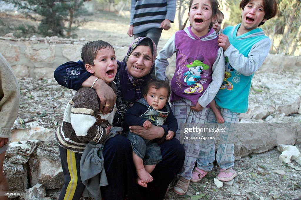 A Syrian woman and her children cry amongst the destroyed houses in Azaz town of Aleppo, Syria, December 28, 2013. Four people were killed and many others were wounded in the Syrian Army air strike on Azaz town.