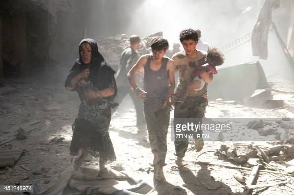 A Syrian woman and youths one of them carrying a wounded baby flee the site of a reported barrelbomb attack by Syrian government forces in the...