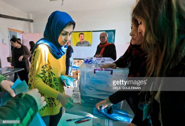 A Syrian woman arrives to cast her vote in local elections held in the northeastern Syrian city of Qamishli on December 1 with a flag depicting the...