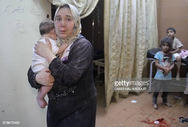 Syrian woman carries a baby inside a makeshift hospital following strikes and shelling on the rebelheld northwestern city of Idlib late on July 21...