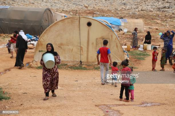 Syrian woman carries a bucket during Muslim's holy month of Ramadan in Idlib Syria on June 23 2017 Ahead of Eid al Fitr Syrian people who fled from...