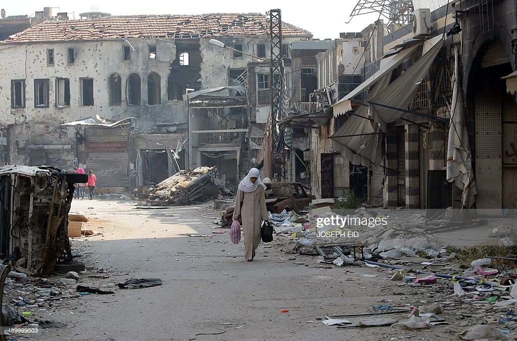 A Syrian woman carries bags on May 12 2014 in a destroyed neighbourhood of the Old City of Homs some 162 kilometres north of the capital Damascus...