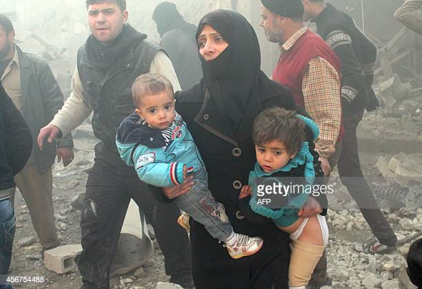 A Syrian woman carries children following airstrikes on a rebel area of the wartorn northern city of Aleppo on December 15 2013 The Aleppo Media...